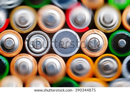 Several batteries are next to each other. Many aa batteries. Energy abstract background of colorful batteries. Close up top view on rows of selection of AA batteries. Alkaline battery aa size.