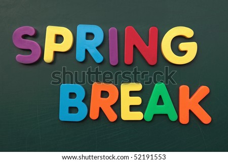 Several bold multicolored letters build the term spring break on a blackboard. - stock photo
