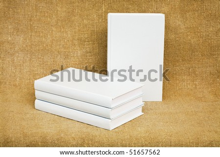 Several books on the background of brown canvas - stock photo