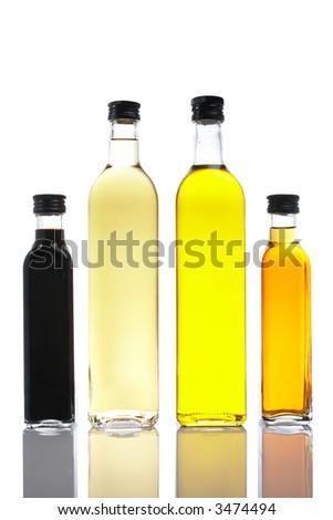 Several bottles of olive oil and vinegar reflected on white background - stock photo