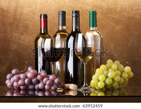 Several bottles of white and red wine, two glasses and grapes on a golden background - stock photo