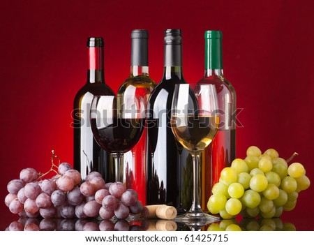 Several bottles of white and red wine, two glasses and grapes on a red background - stock photo
