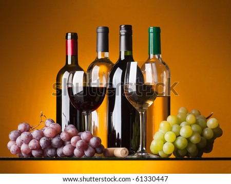 Several bottles of white and red wine, two glasses and grapes on an orange background