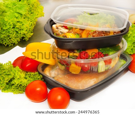 Several boxes for lunch with salad, chicken - stock photo