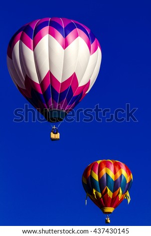 Several brightly colored hot air balloons aloft in early morning blue sky