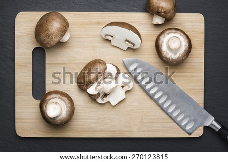 Several brown sliced champignon mushrooms on a wooden chopping board with knife, with dark grey slate stone background. - stock photo