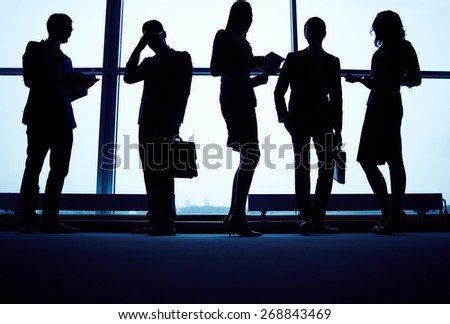 Several business partners having meeting by office window - stock photo