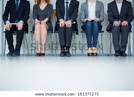Several business people sitting on chairs in a row - stock photo