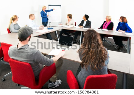 Several businesspeople meeting in a spaceous meeting room for a presentation - stock photo