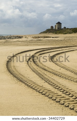 several car tracks in the sand with windmills on the background - stock photo