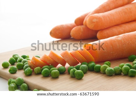 Several carrots (one sliced) and green peas on a wooden cutting board - isolated on white background - stock photo