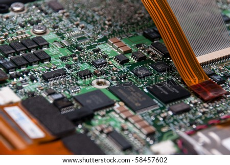 Several circuits in a green computer circuit board with attached electrical ribbon. - stock photo