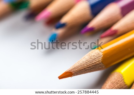 Several color pencils on a white paper sheet - stock photo