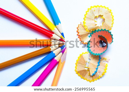 several colored pencils and shavings on white background with copy space - stock photo