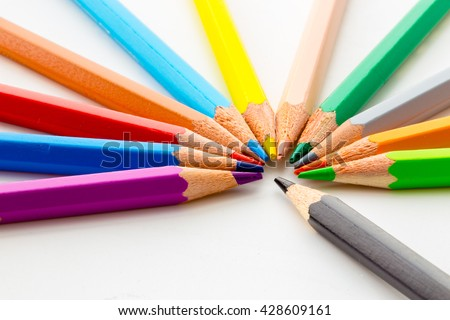 Several colored pencils in a circle with one black pencil pointing to the center - stock photo