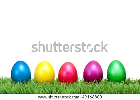 Several Colorful Easter eggs lying in a row on a green meadow. Isolated on white background. - stock photo