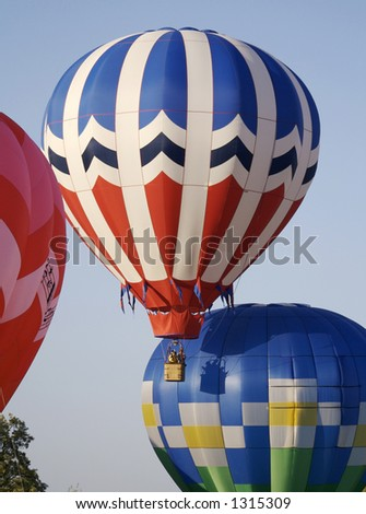 Several colorful hot air balloons launch into a bright blue sky - stock photo
