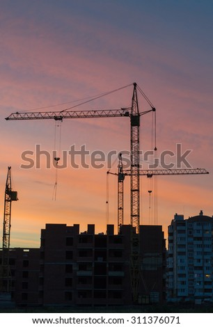 several construction cranes near the high-rise buildings