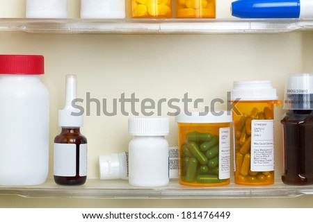 Several containers of over the counter and prescription medications on the shelves of a 1960's medicine cabinet.  - stock photo