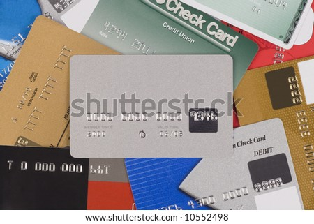 Several credits cards in a pile with a silver one in the center. All recognized names have been removed - stock photo