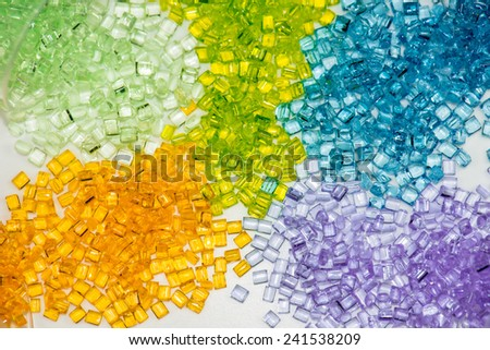 several different dyed polymer granulates in laboratory on table - stock photo