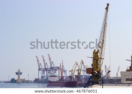 Several different harbor cranes and ship in the sea port