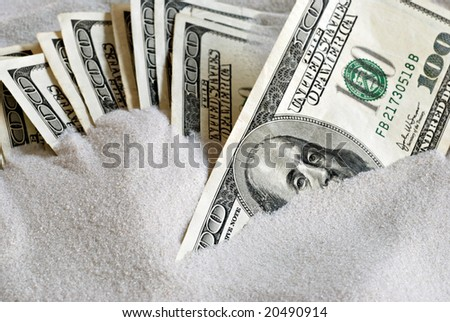 Several 100 dollar bills partially buried in sand.  Conceptual image depicting a safer alternative to investing.  Macro with shallow dof.