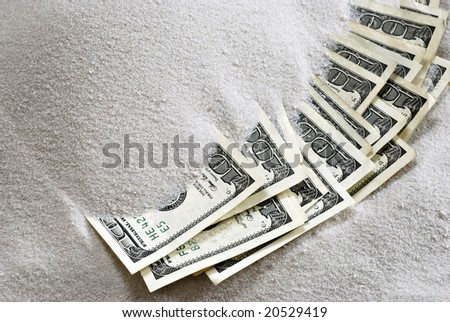 Several 100 dollar bills partially buried in sand.  Conceptual image depicting a safer alternative to investing.  Close-up with copy space.