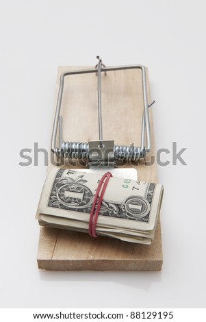 several dollar bills with elastic band  set on a mouse-trap - stock photo