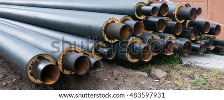 several dozen black pipes with insulation. pipes for supplying gas or heat pressure medium.
