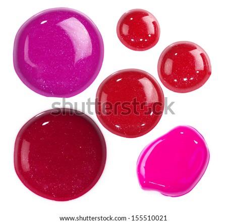 Several drops of red and pink nail polish, lip gloss bulk - stock photo