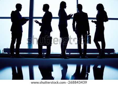 Several employees communicating by office window - stock photo