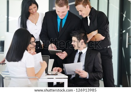 Several employees discussing new ideas in groups at meeting