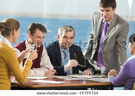 Several employees voicing their ideas to senior boss in office - stock photo