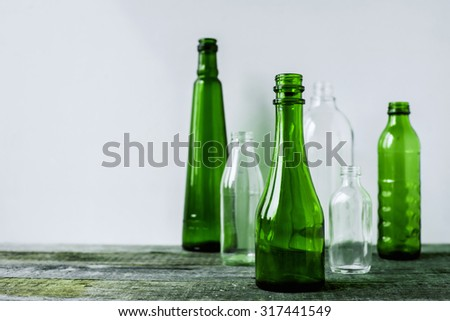 several empty glass bottles on vintage wooden background - stock photo