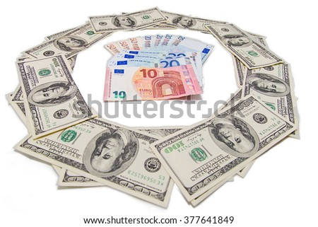 Several Euro bills in a circle of American dollar banknotes. - stock photo