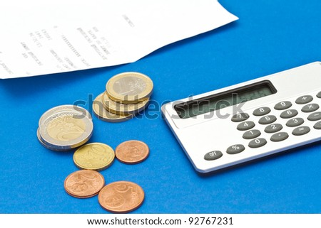 Several euro coins, bill and calculator on blue background - stock photo