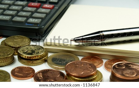several euro coins notepad pen and calculator