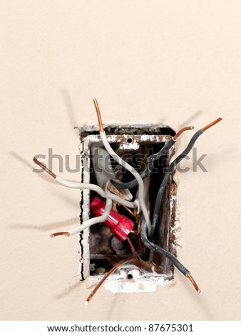 Several exposed copper wires protruding from a beige wall. - stock photo
