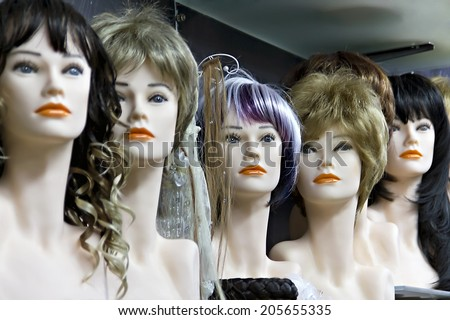 Several female mannequins with wigs on the shelf - stock photo