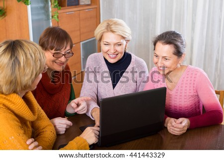 Several female pensioners browsing web on laptop indoor