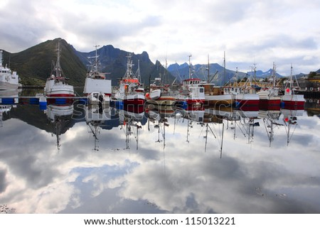 several fiching ships moored to the wharf. Senja island, Norway - stock photo