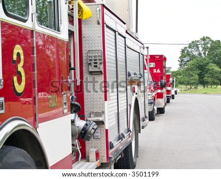 Several fire trucks parked one behind the other on a quiet street. - stock photo