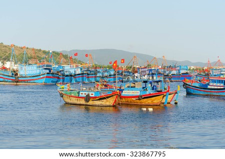 several Fishing boats with red flags in marina at Nha Trang, Vietnam