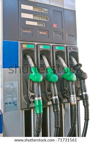 Several gasoline pump nozzles at petrol station - stock photo