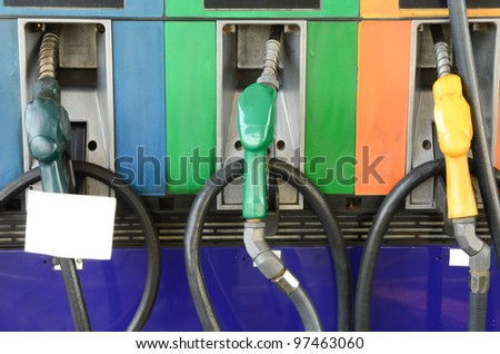 Several gasoline pump nozzles with white paper at petrol station - stock photo