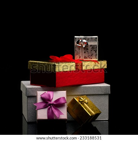 several glamour  gift boxes with bows on dark reflection  background
