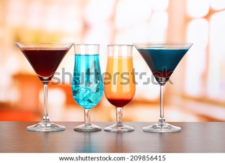Several glasses of different drinks on bright background