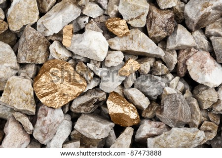 Several golden nuggets in a rocky river bed. - stock photo