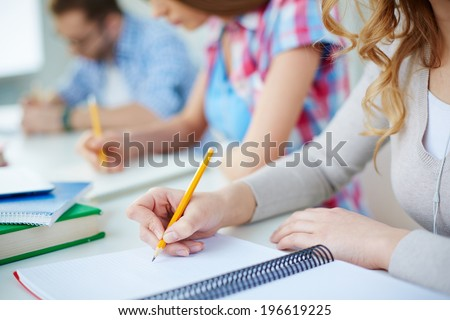 Several groupmates carrying out written task or writing lecture - stock photo